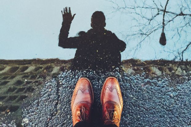person-waving-at-reflection-in-street-puddle (1)